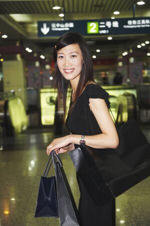 grampa: Asian woman carrying shopping bags in subway