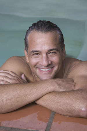 1 person: Hispanic man leaning on edge of swimming pool