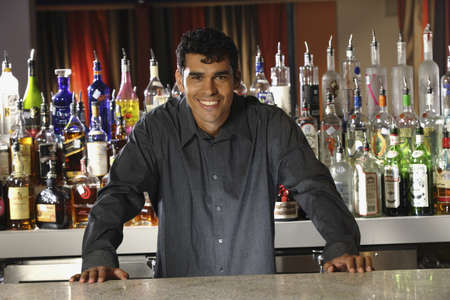 barkeep: Hispanic male bartender leaning on bar LANG_EVOIMAGES