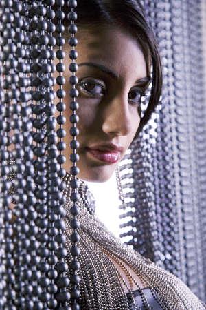 Portrait of Hispanic woman in beaded curtain