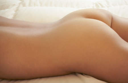 Nude Asian woman laying on bed