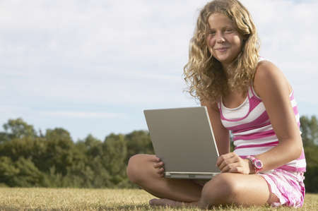 unconcerned: Girl using laptop in field