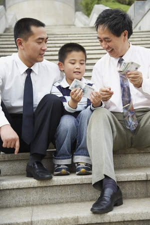 gramma: Asian grandfather, father and son looking at money