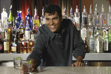 Hispanic male bartender serving drink LANG_EVOIMAGES