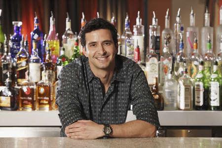 saturating: Hispanic male bartender leaning on bar LANG_EVOIMAGES