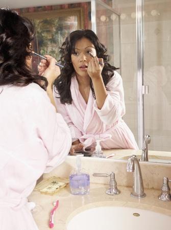 pj's: Hispanic woman applying make up in bathroom mirror LANG_EVOIMAGES