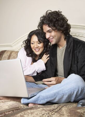 facing away: Hispanic couple online shopping in bed