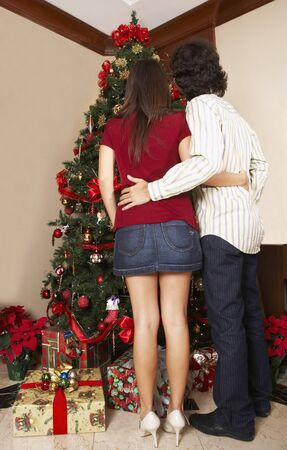 Hispanic couple looking at Christmas tree