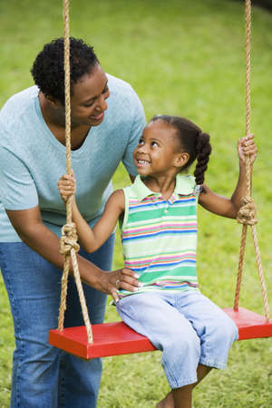 playthings: African mother pushing daughter on swing