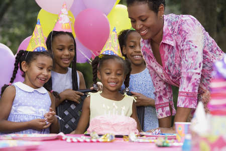 birthday party kids: African girl and cake at birthday party