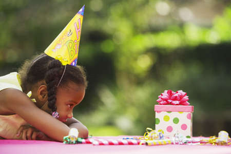 african american mother and daughter: African girl looking at birthday gift