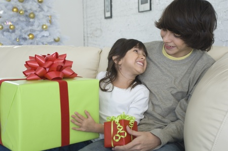 fathering: Hispanic brother and sister exchanging Christmas gifts
