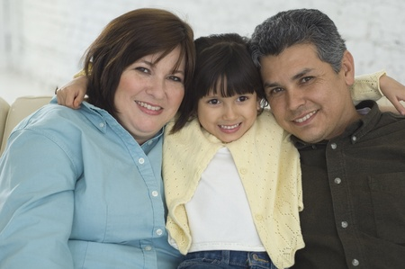 Hispanic parents and daughter hugging Stock Photo
