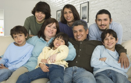 holding family together: Portrait of Hispanic family on sofa LANG_EVOIMAGES
