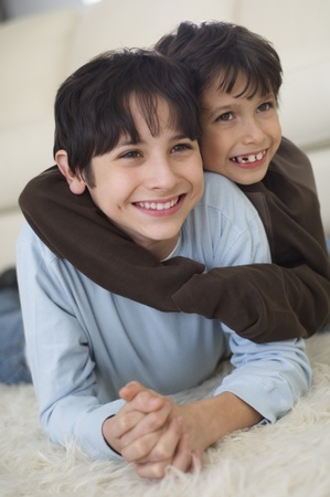 davenport: Hispanic brothers hugging on floor LANG_EVOIMAGES