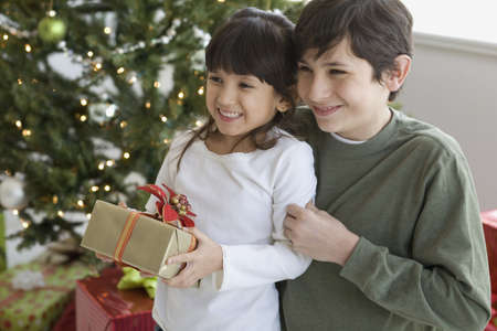 sloping: Hispanic brother and sister holding Christmas gift LANG_EVOIMAGES