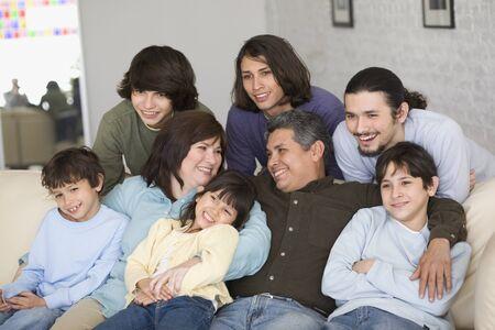 Portrait of Hispanic family on sofa LANG_EVOIMAGES