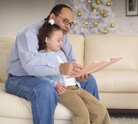 davenport: Hispanic grandfather reading to granddaughter LANG_EVOIMAGES