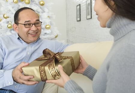 poppa: Hispanic woman giving gift to man LANG_EVOIMAGES