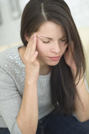 giver: Hispanic woman rubbing head LANG_EVOIMAGES