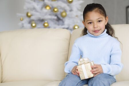 Hispanic girl holding Christmas gift
