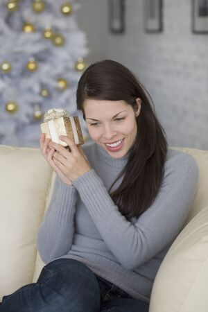 davenport: Hispanic woman shaking Christmas gift LANG_EVOIMAGES