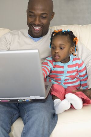 poppa: African father and daughter looking at laptop