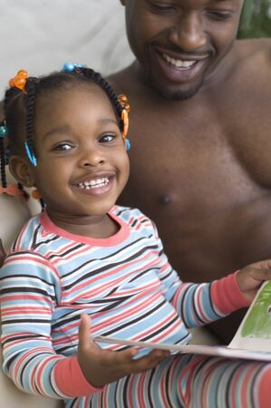 African father reading to daughter 免版税图像