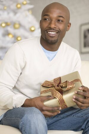 gramma: African man holding Christmas gift