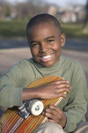 grampa: African boy holding skateboard LANG_EVOIMAGES