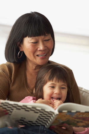dubious: Asian grandmother reading to granddaughter