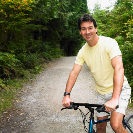 adventuresome: Man riding bicycle on nature trail LANG_EVOIMAGES