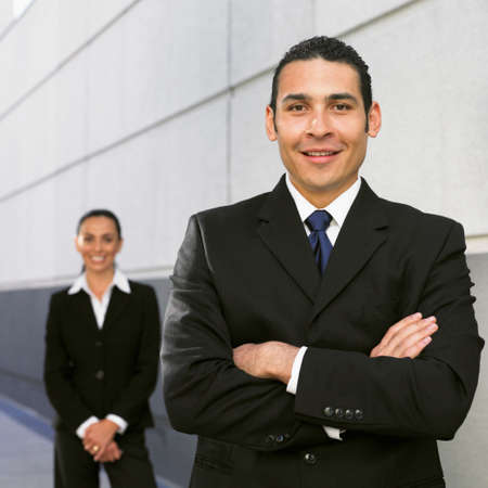 talker: Hispanic businessman with coworker in background