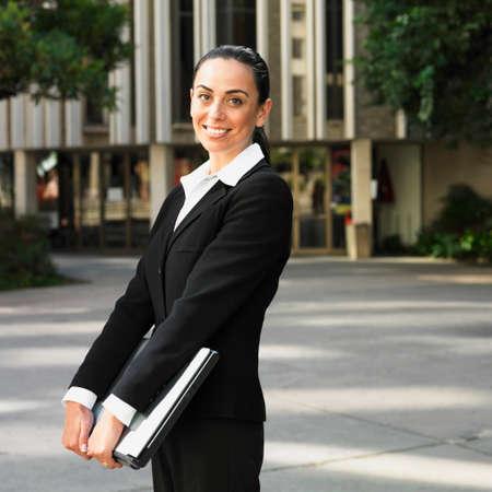 talker: Hispanic businesswoman holding laptop outdoors