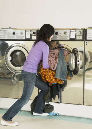 mischeif: Asian woman in laundromat LANG_EVOIMAGES