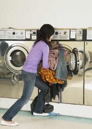 laundromat: Asian woman in laundromat LANG_EVOIMAGES
