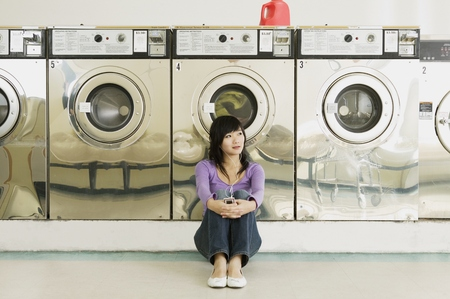 Asian woman in laundromat 스톡 콘텐츠