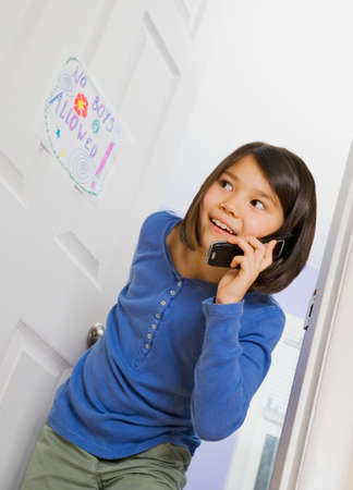 low spirited: Asian girl talking on cell phone LANG_EVOIMAGES