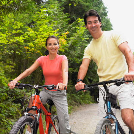 only one mid adult man: Couple riding bicycles on nature trail LANG_EVOIMAGES
