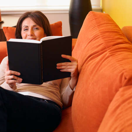 davenport: Hispanic woman reading on sofa LANG_EVOIMAGES