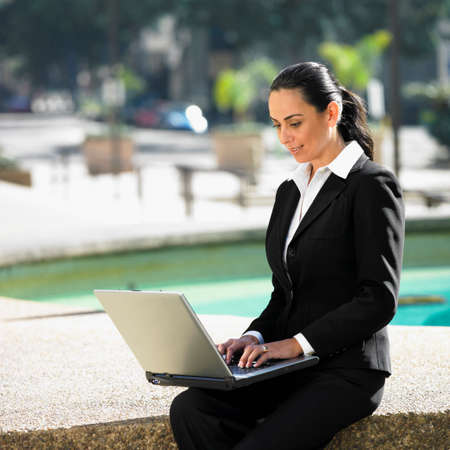 concluding: Hispanic businesswoman typing on laptop LANG_EVOIMAGES