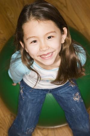 Asian girl sitting on ball
