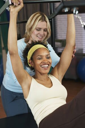 personal information: African woman exercising with personal trainer