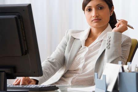 bellybutton: Indian businesswoman sitting at desk