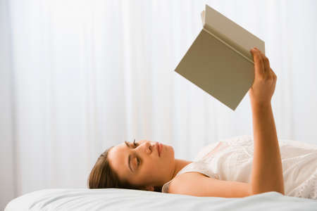 lighthearted: Woman reading on bed