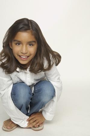 Close up of Hispanic girl crouching