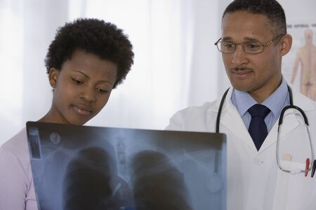 conferring: African male doctor and patient looking at x-ray