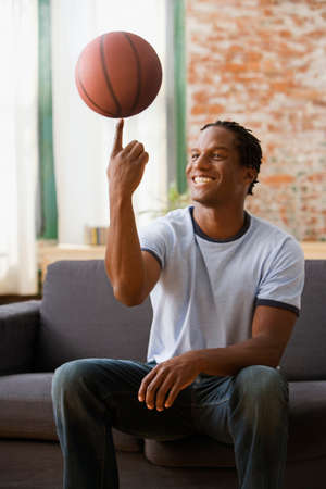 prevailing: African man spinning basket ball on finger