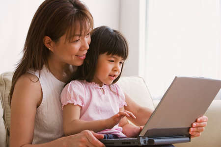 motioning: Asian mother and daughter looking at laptop