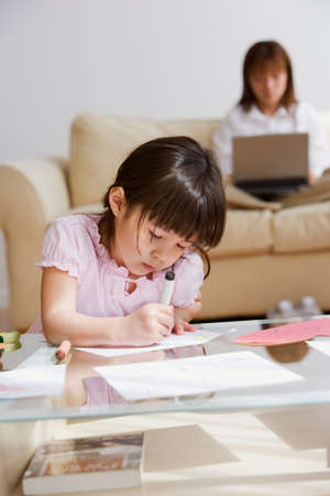 telecommuter: Asian girl coloring with mother in background